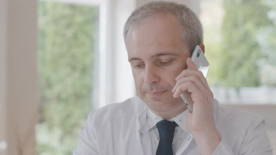 Thumbnail for Close-up of Confident Male Doctor Talking on the Phone. Portrait of Professional Physician