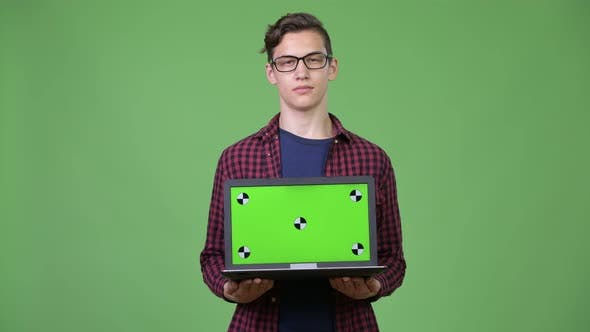 Thumbnail for Young Handsome Teenage Nerd Boy Showing Laptop