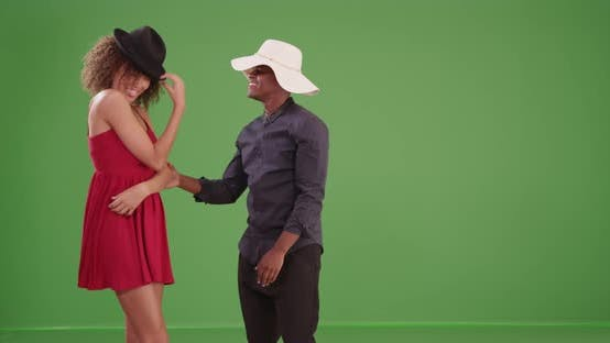 Thumbnail for Young black man and woman play with hats on green screen
