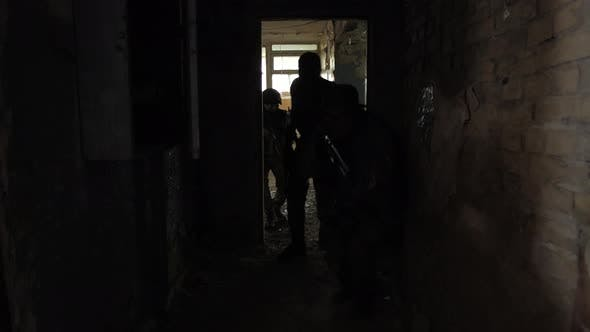 Group of Soldiers in Darkness Storming Building
