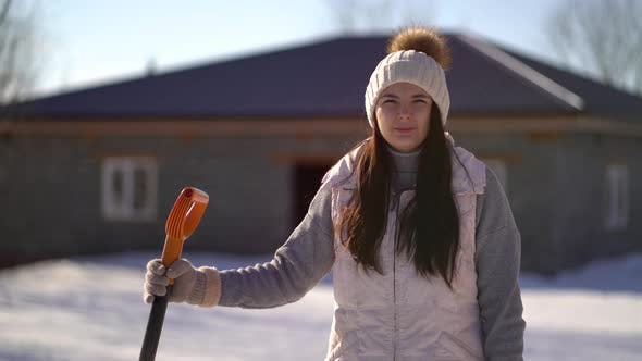 Thumbnail for Young Girl Stands with a Shovel in the Backyard. Woman Ready To Clear Snow After Snowfall