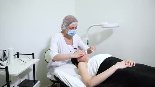 Beauty Salon Specialist Removing Lotion From Neck and Face of Woman