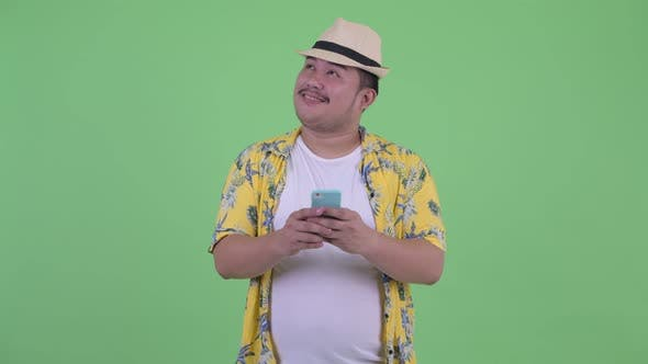 Thumbnail for Happy Young Overweight Asian Tourist Man Thinking While Using Phone