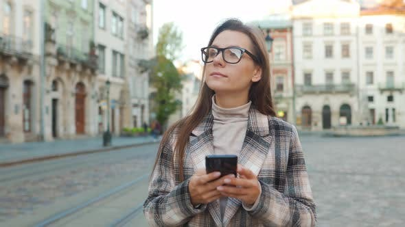 Woman Walking Down an Old Street and Using Smartphone