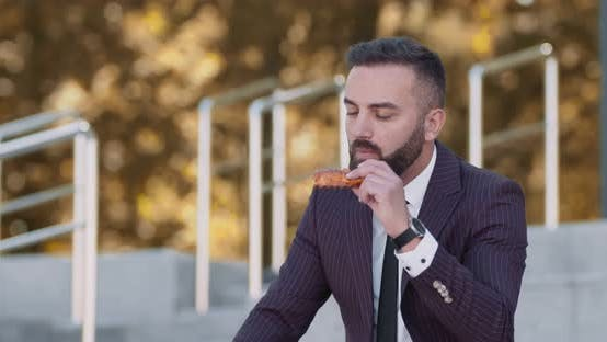 Thumbnail for Middle Aged Businessman Eating Pizza in Autumn Park, Resting From Office