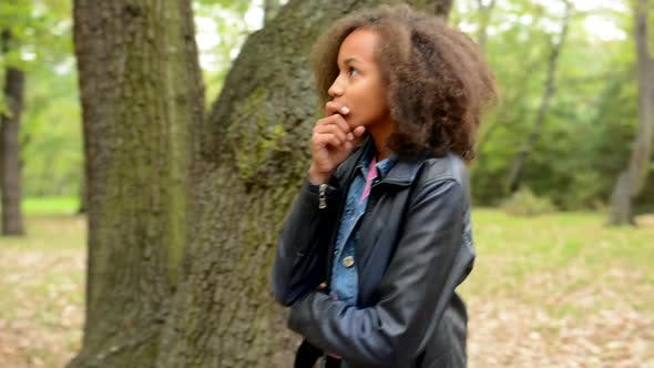 Thumbnail for Young African Beautiful Thoughtful Girl Walk Around Big Tree and Think About Problems