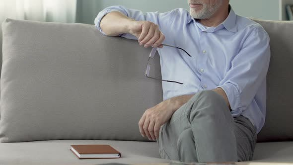 Thumbnail for Experienced male psychologist sitting on couch, listening to patient, session