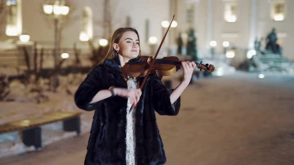 Thumbnail for Young Girl in a Black Coat is Playing the Violin