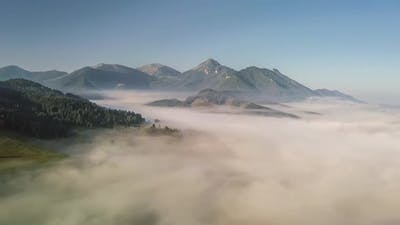 Fly over Foggy Mountains in Sunny Morning