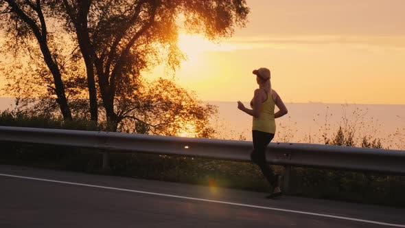 Thumbnail for Middle Aged Woman Jogging By the Lake at Sunset