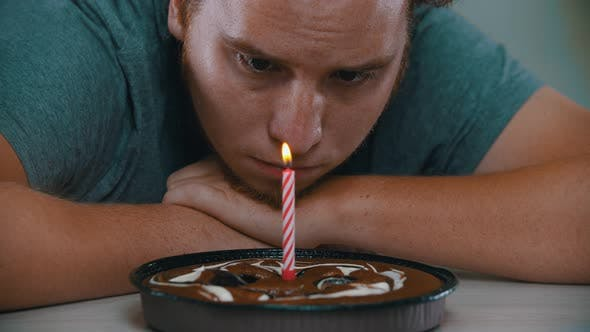 A Man Is Looking at a Candle on the Cake