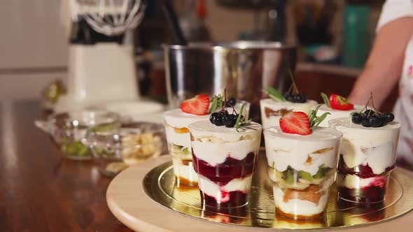 Glasses with Sweet Fruit Mousse with Cream Are Standing in a Round Plate