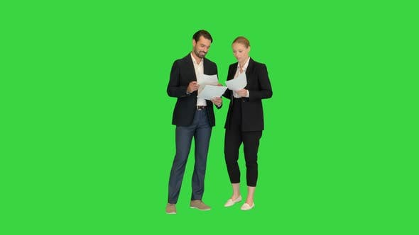 Two Young Business People Talking About Documents on a Green Screen Chroma Key