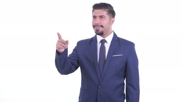 Happy Bearded Persian Businessman Pointing Finger and Directing