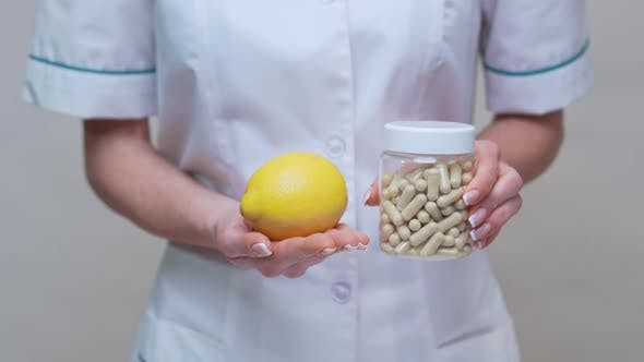 Nutritionist Doctor Healthy Lifestyle Concept - Holding Organic Lemon Fruit and Jar of Vitamin Pills