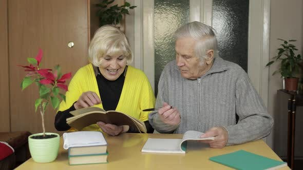 Thumbnail for Happy Old Mature Retired Couple Sit on Table at Home Enjoying Free Time Leisure