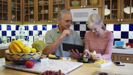 Thumbnail for Senior couple using tablet computer in kitchen during lunch