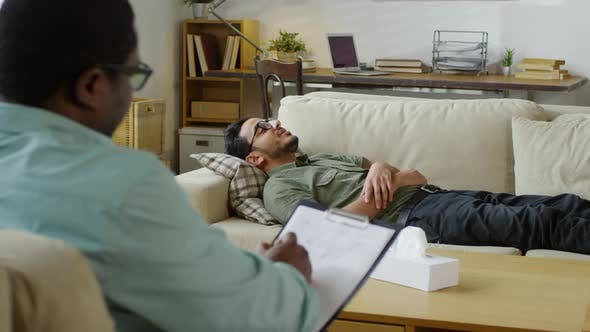 Thumbnail for Young Middle Eastern Patient Lying on Sofa and Talking to Psychotherapist
