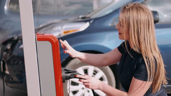 Thumbnail for A Woman Is Charging an Electric Car at the Charging Station