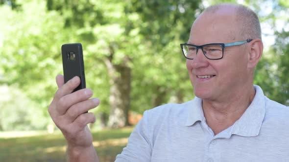 Thumbnail for Face Of Happy Senior Man Using Phone At The Park