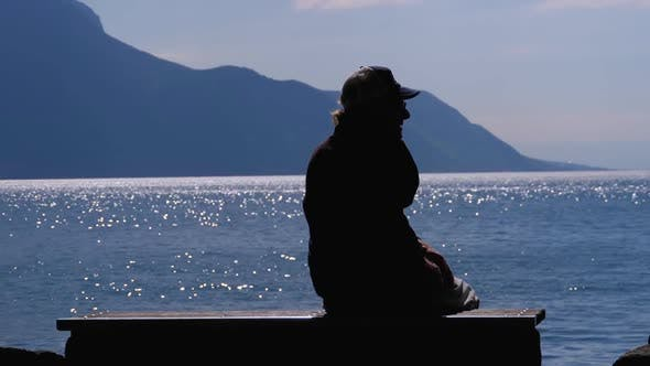Thumbnail for Silhouette of a Lonely Aged Man Sitting on a Bench on Backdrop of a Lake and Mountains