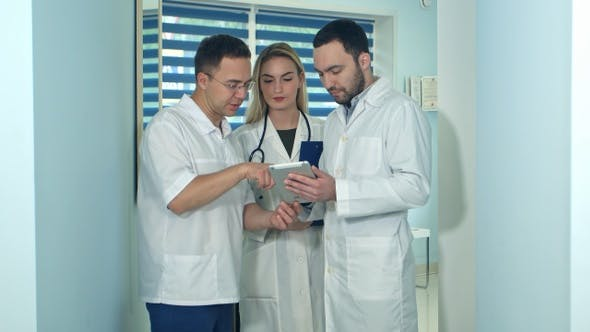 Thumbnail for Male doctor showing something on tablet to his colleagues