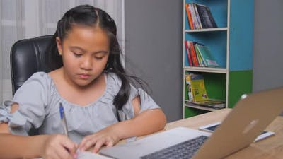 Little Girl E-Learning With Laptop At Home
