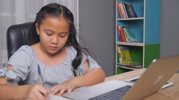 Kleines Mädchen E-Learning mit Laptop zu Hause