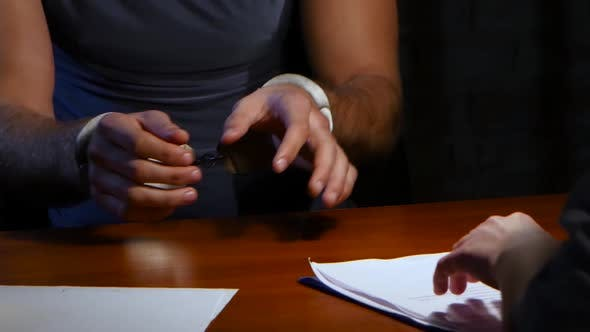 Closeup. Criminal in Handcuffs Is Required To Write Confessionary Statements
