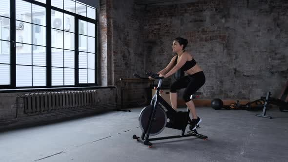 Active young asian woman enjoying cycling exercise at gym having positive emotion