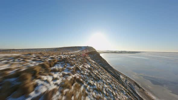 Snowy Patches Bright Sky Calm Ocean Waters  FPV Drone Shot