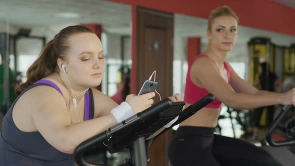 Thumbnail for Lazy Obese Girl Looking at Slim Blonde Training Actively on Stationary Bike