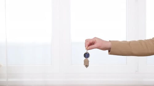 Man and Woman Shake Hands Giving Over Keys To Apartment