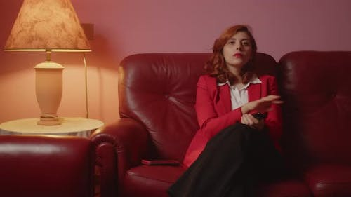 Beautiful girl with red jacket sitting on the sofa in the living room
