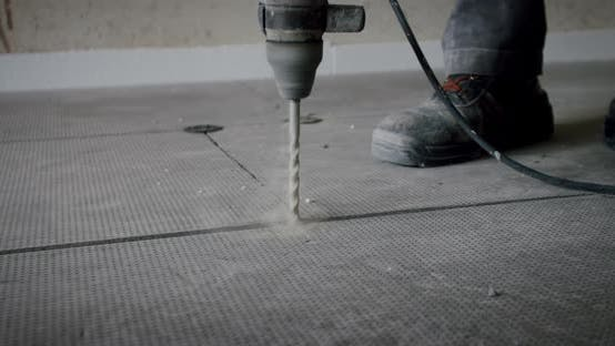 Thumbnail for the Worker Drills Holes for Installation of a Heat-insulated Floor. Close Up.