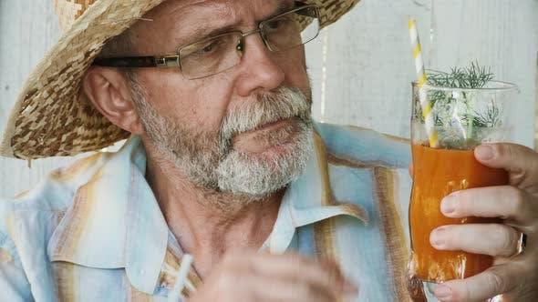 Thumbnail for Senior Man Tastes Orange Smoothie