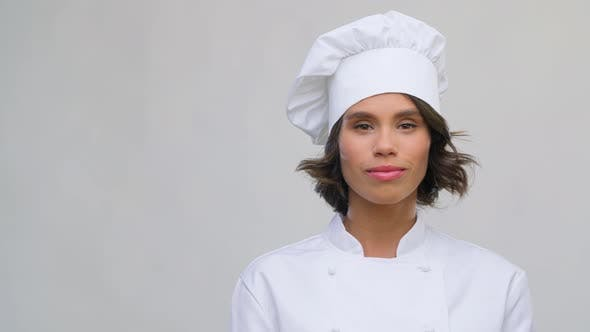 Portrait of Smiling Female Chef in Toque Over Grey