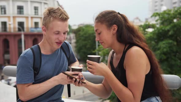 Thumbnail for Two Young People Talking, Drinking Coffee and Using Smartphone in City