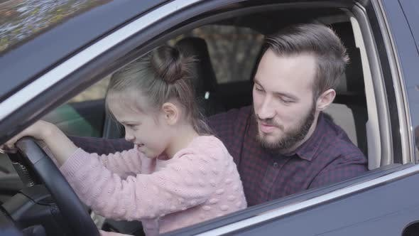 Thumbnail for Portrait Little Girl Sitting on Father's Lap in the Car Close Up. The Child Is Learning To Drive the