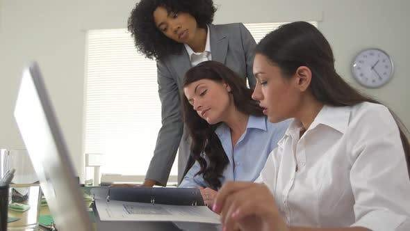 Group of diverse business women working together at laptop computer