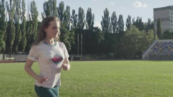 Thumbnail for Athletic Young Girl Runs in the Stadium. Slow Motion