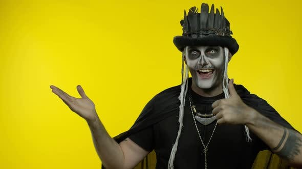 Sinister Man with Horrible Halloween Skeleton Makeup Trying To Scare, Pointing To the Left
