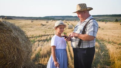 Little Girl with Grandfather in Field Haystacks, Grandfather Farmer Is Teaching the Younger