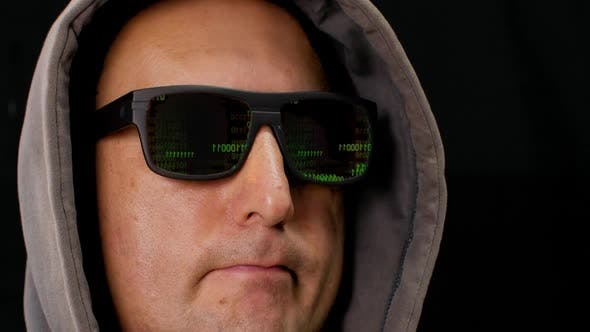 Green Binary Code Is Reflected in the Black Glasses of the Hacker's Glasses. Computer Hacker in