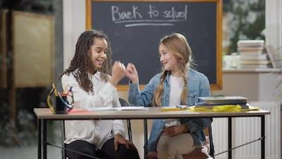 Pinky Swear of Smiling Cute Schoolgirls in Classroom