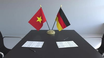 Flags of Vietnam and Germany and Papers on the Table