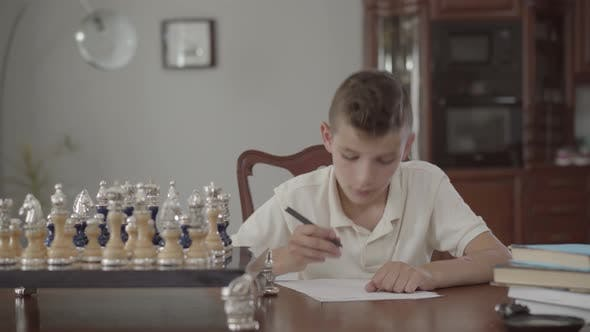 Thumbnail for Portrait of Adorable Thoughtful Guy Sitting at the Table at Home. Boy Dawned on and Writing