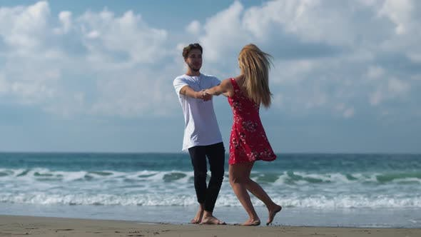 Thumbnail for Young Guy and a Beautiful Girl Happily Spinning with Each Other on the Shore