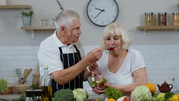 Senior Woman and Man Feeding Each Other with Fresh Raw Vegetable Salad. Eco Food Eating Diet