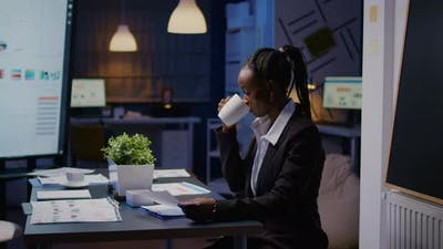 Workaholic African American Businesswoman Analysing Marketing Statistics on Paperwork